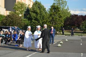 Twin girls dressed in the white gowns are congratulated by BHS principal