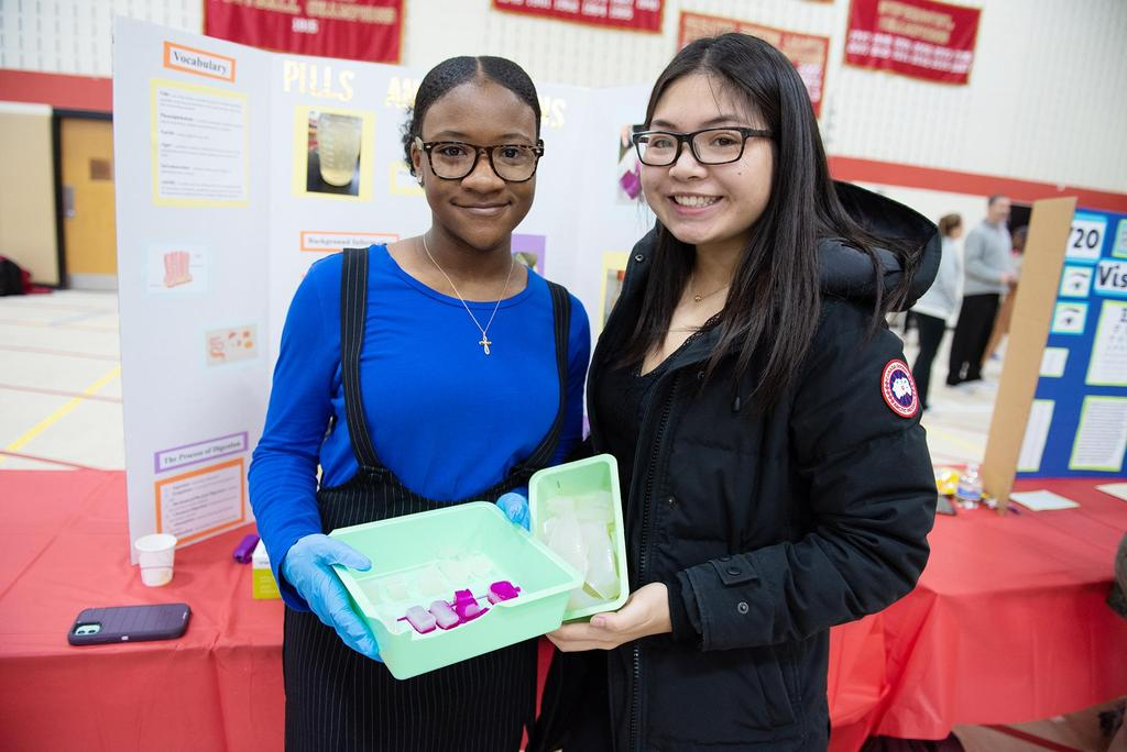 Two female students hold a small plastic container of materials