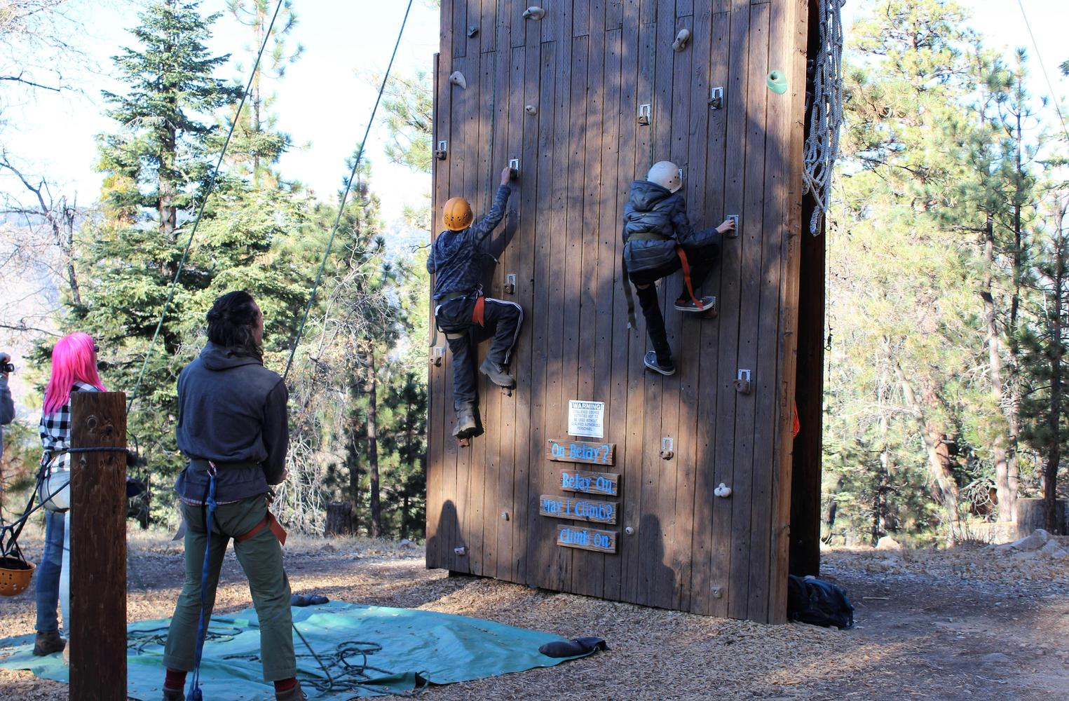 two students climbing a rock wall