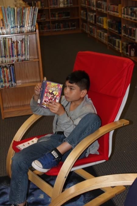 Mission Junior High student lounging in the Library reading a book.