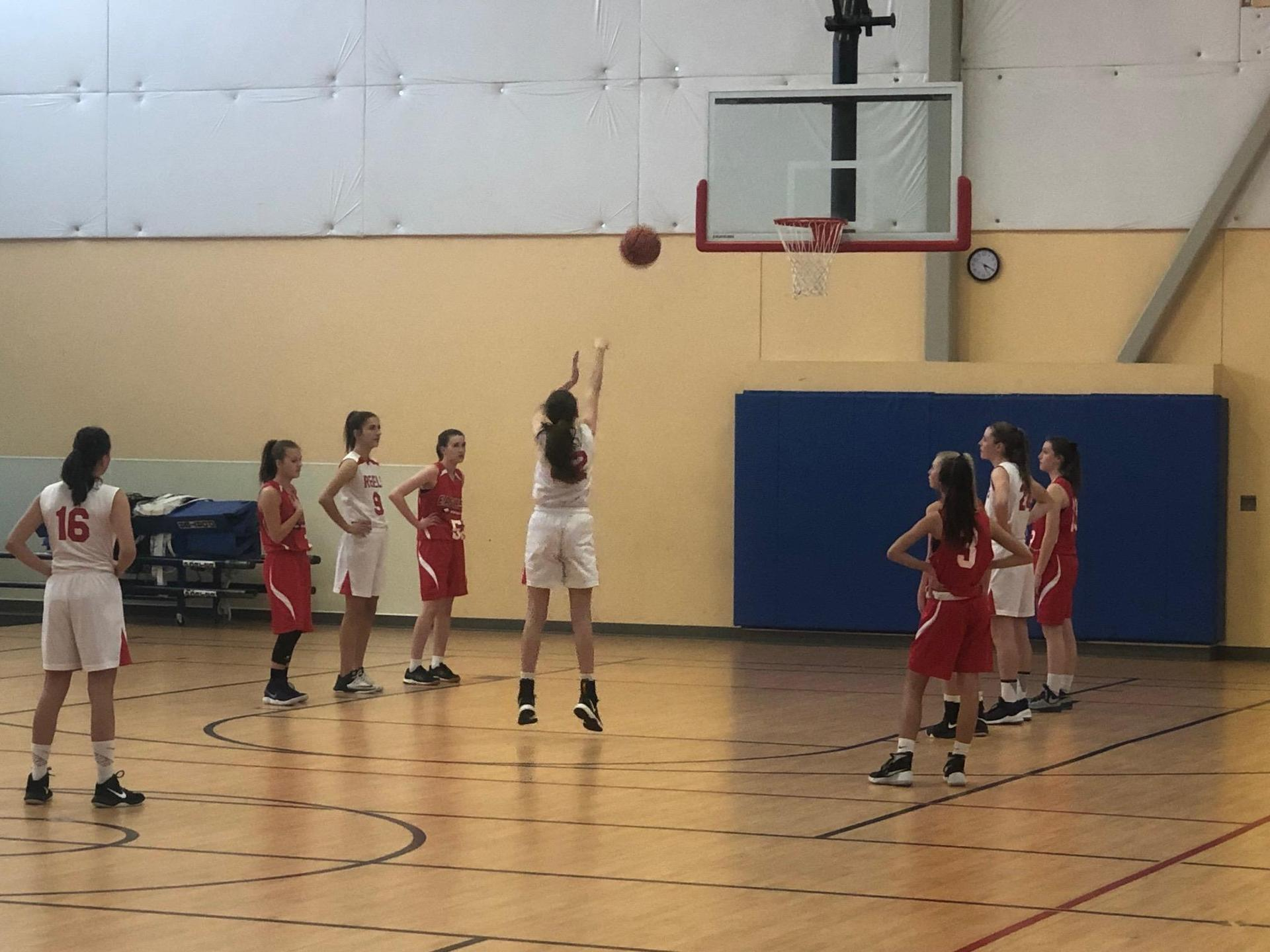 Girls basketball player shooting free throw away from camera