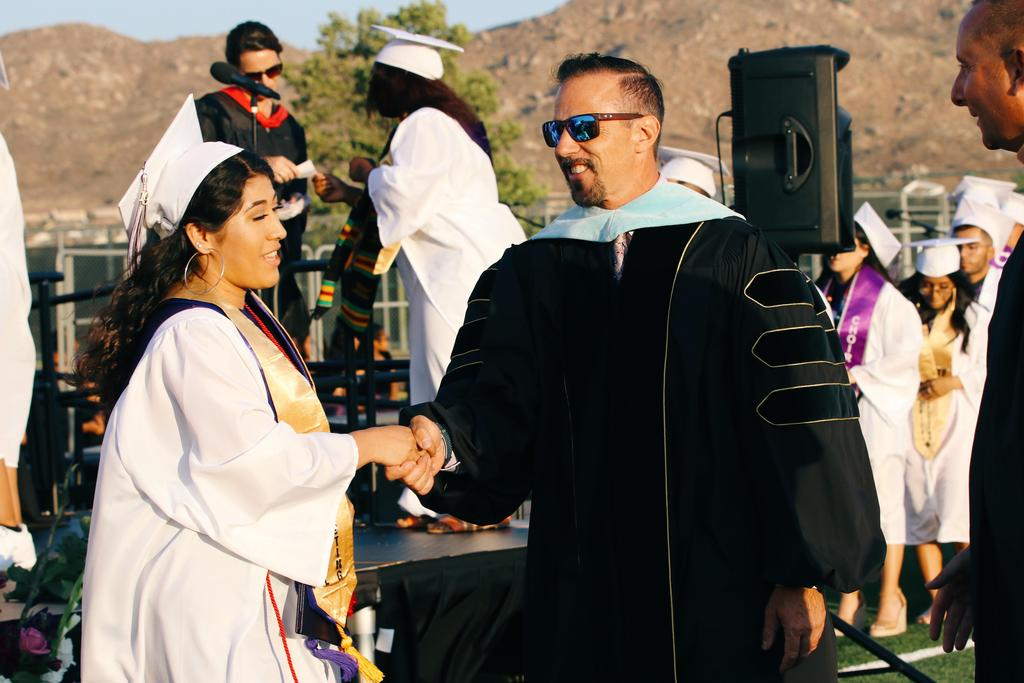 Chief Human Resources Officer Dr. Robert Verdi shakes hand with graduate