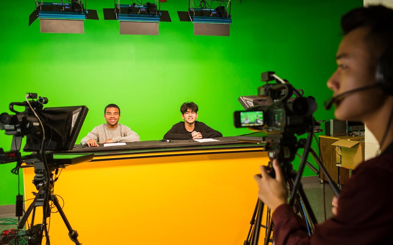Students filming in a school TV studio.
