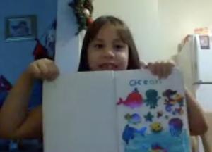 Margaret Oviedo holding up ocean drawing