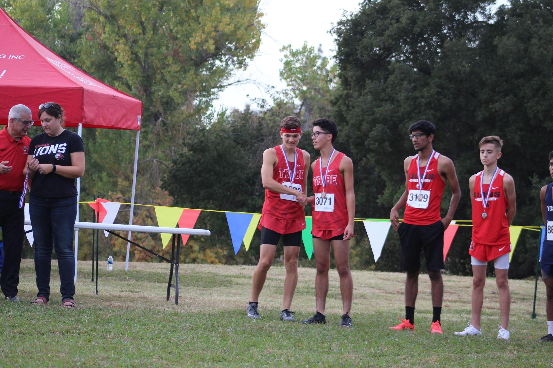 Andrew Castaneda shaking teammate's hand after receiving medal