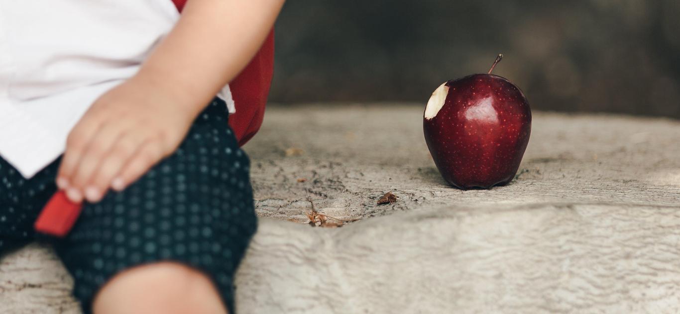 child sitting next to apple