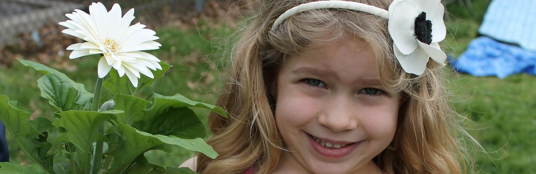 Kindergartner with white flower headband holds white daisy potted plant.