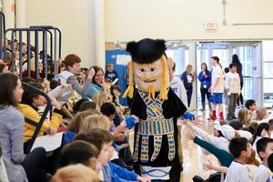 Viking mascot walk through crowd, high fiving kids.
