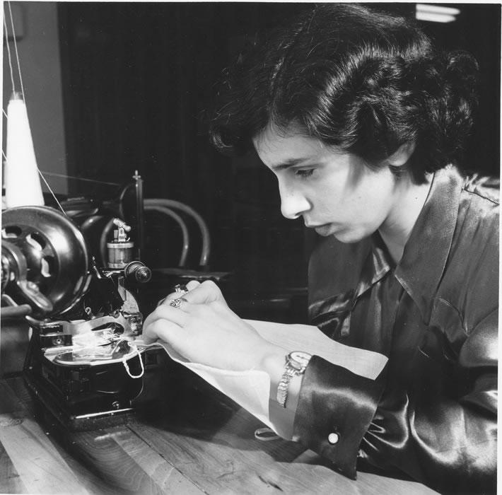 Female student at a sewing maching sewing cloth.