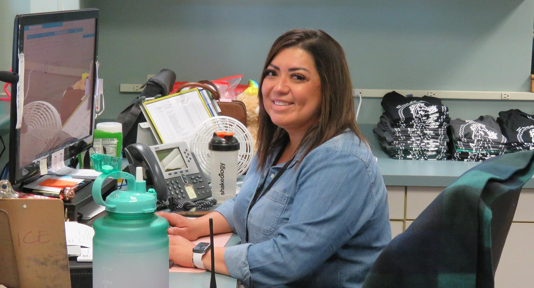 School secretary sitting at her front office desk faces the camera and smiles