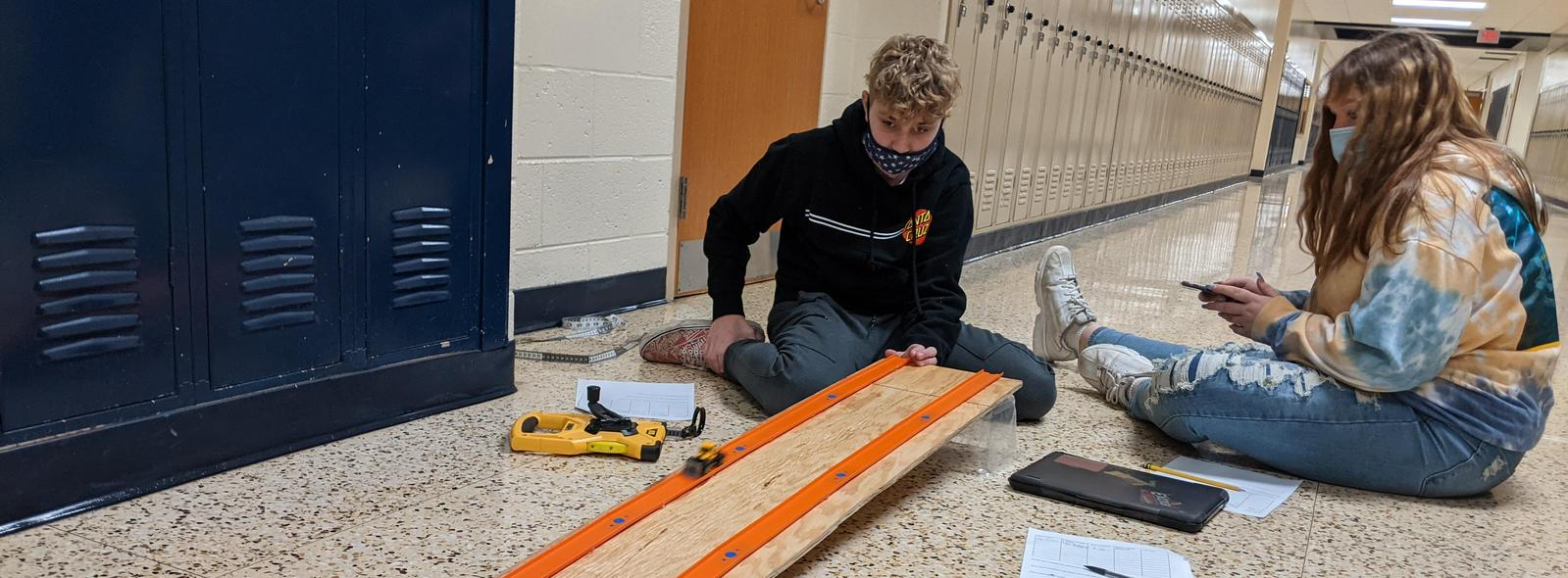 students racing cars on an incline