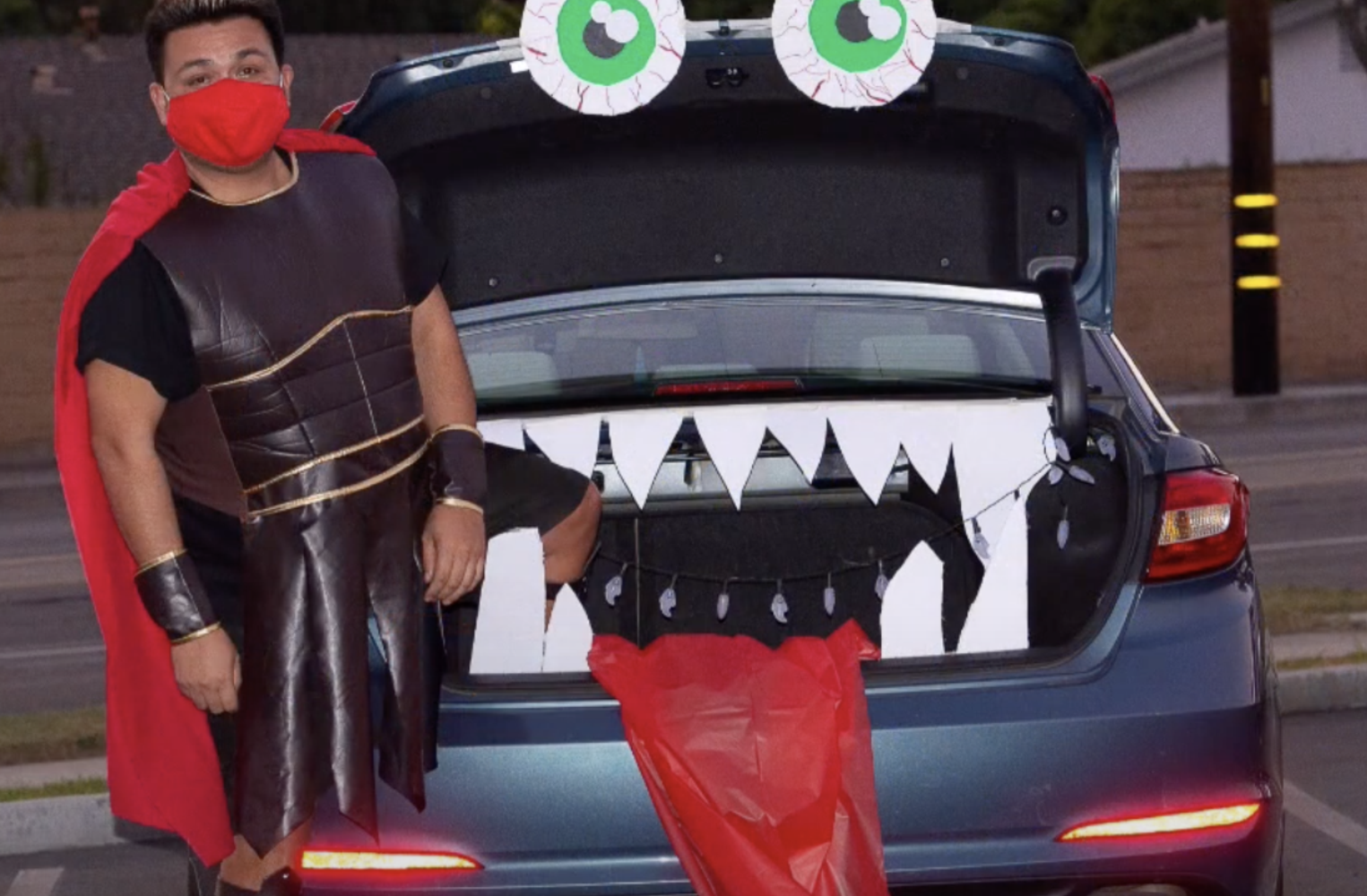 man in costume in front of a monster trunk
