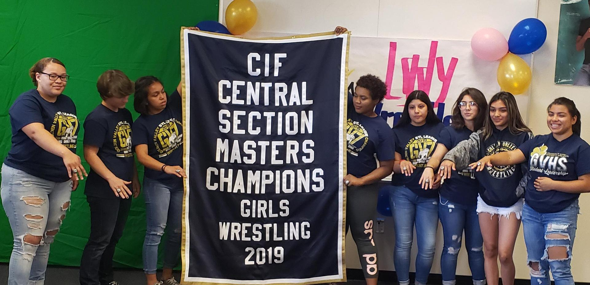 GV girls wrestlers showing the CIF Masters Championship banner