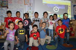 Students showing how strong they are in their superhero t's