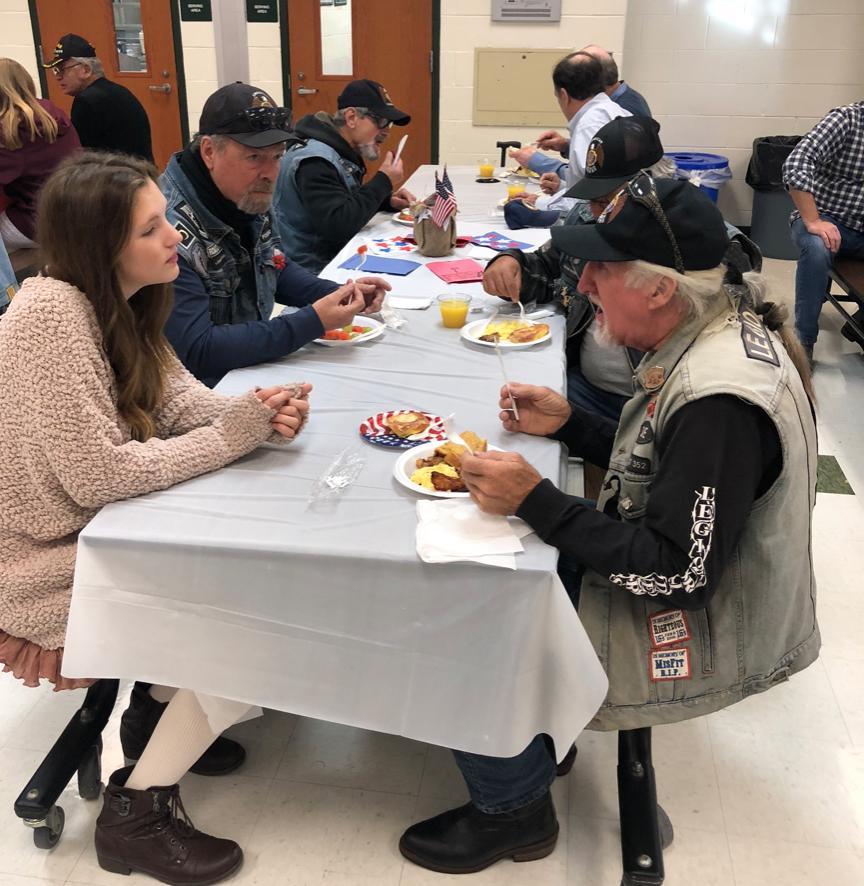 Club members and veterans eating breakfast