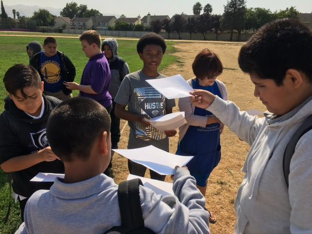 students and a teacher outside in a field looking at papers they are holding up to the sun to get an image of the eclipse