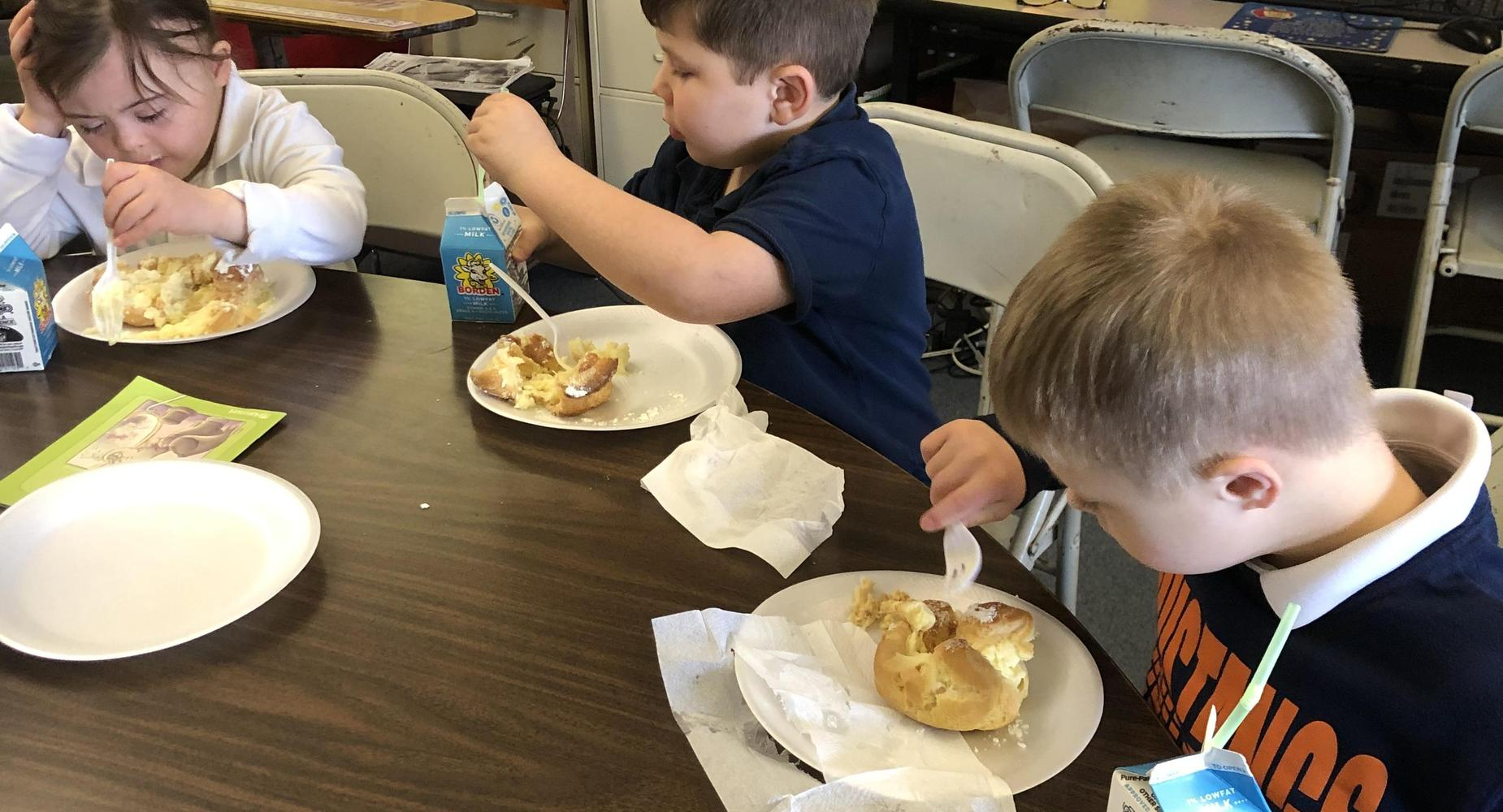 Students eating cream puffs