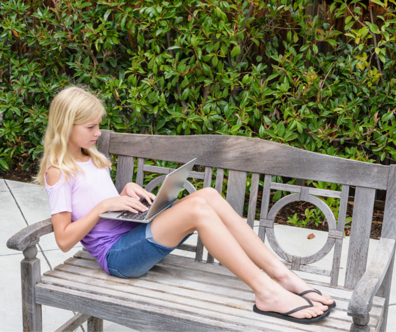girl in shorts on bench with laptop