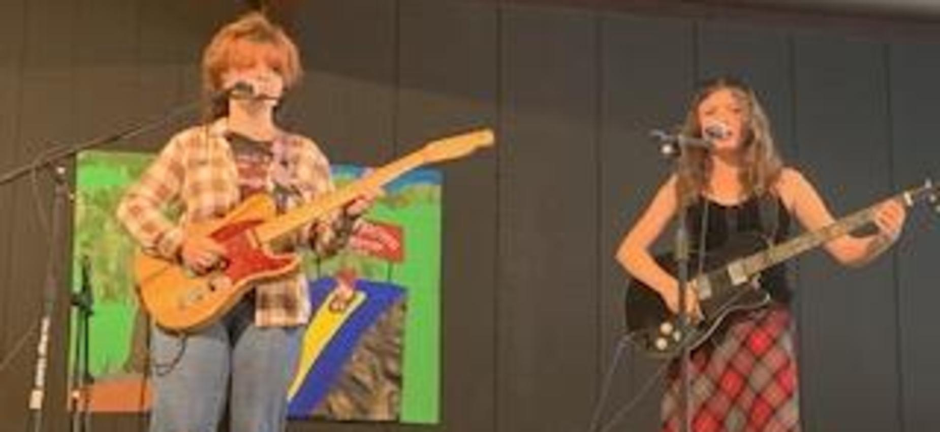 Two girls play guitar and sing on a stage.