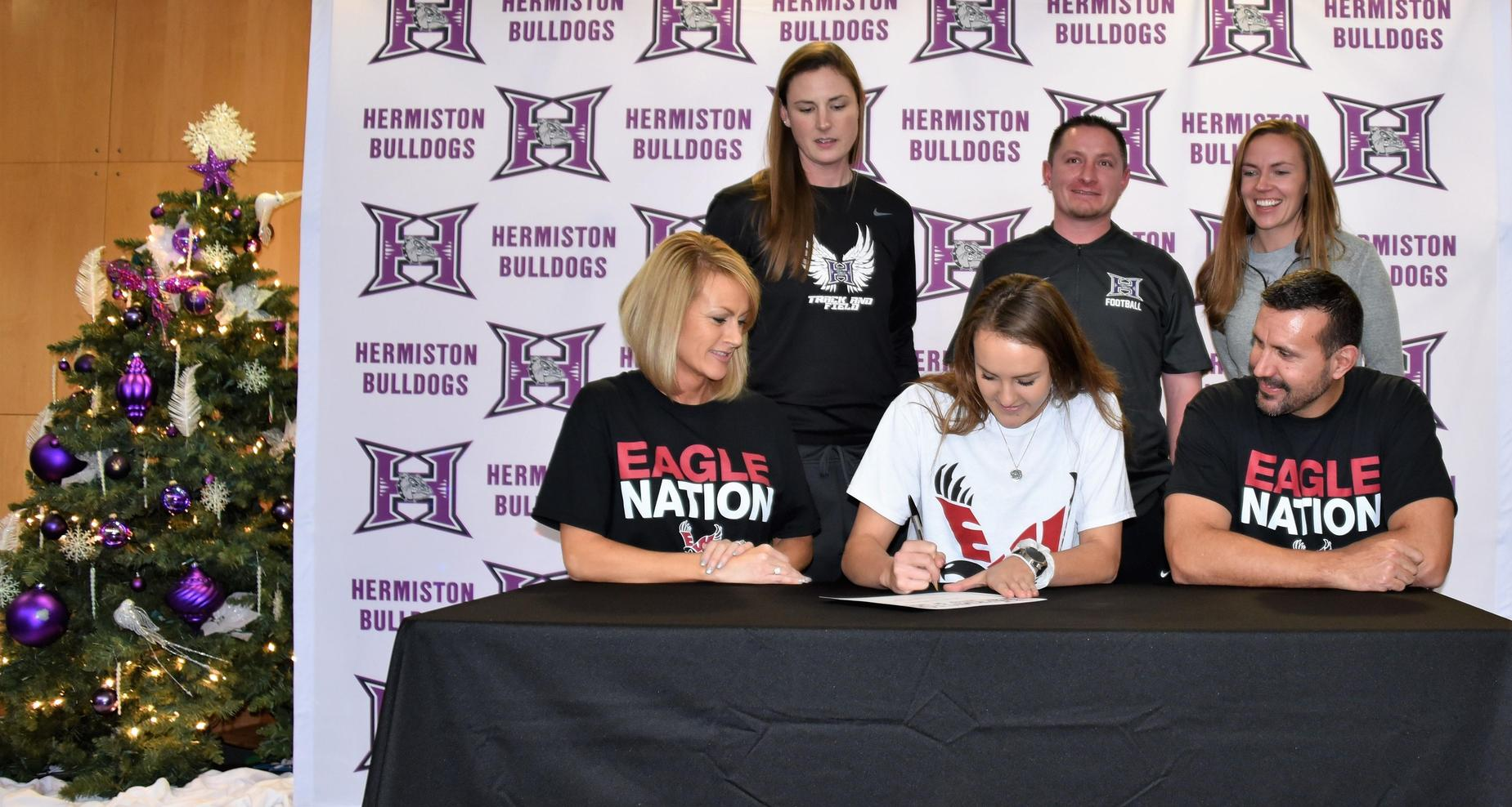 Female student signing her letter of intent surrounded by parents and coaches.