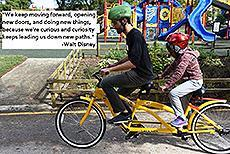 "Image of a student and staff on a tandem bicycle. ""We keep moving forward, opening new doors, and doing new things, because we're curious and curiosity keeps leading us down new paths."" -Walt Disney"