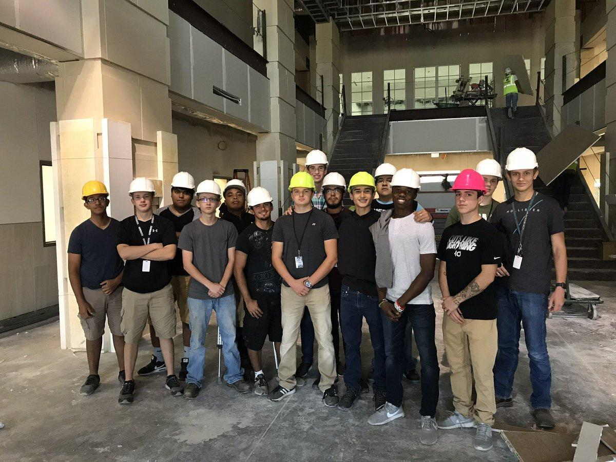 group of building trades students in hard hats on construction site