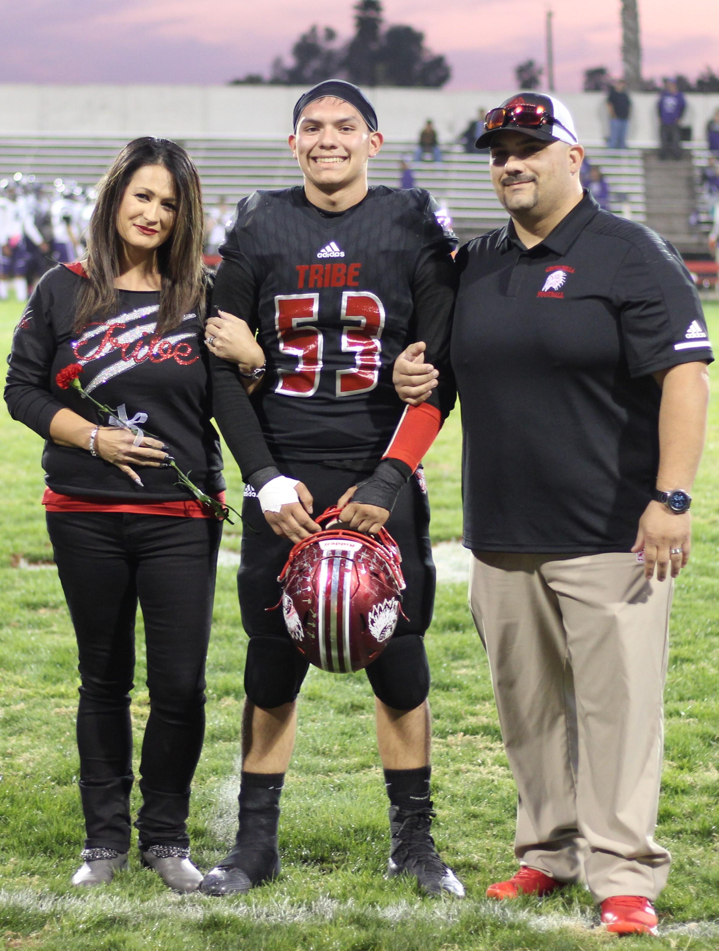 Senior football player Alex Escoto and his escorts.