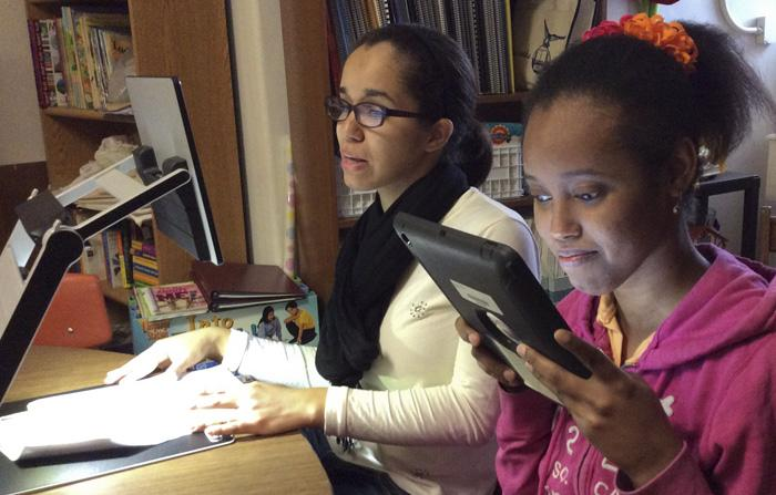 Two female students one using a book magnifier and the other using her iPad