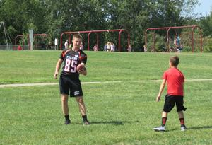 A TKHS football player tosses a football around with a group of students.