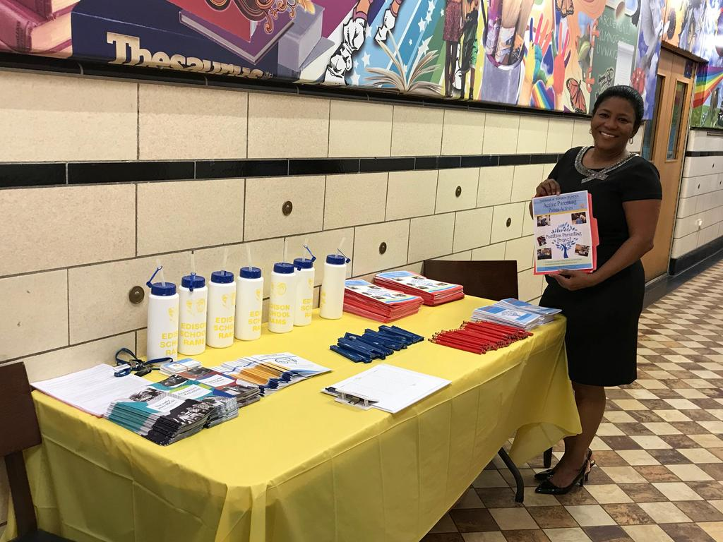parent liaison proudly showing off her display table for parents