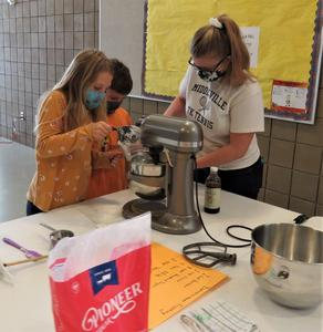 Students learn to measure ingredients and use a mixer.