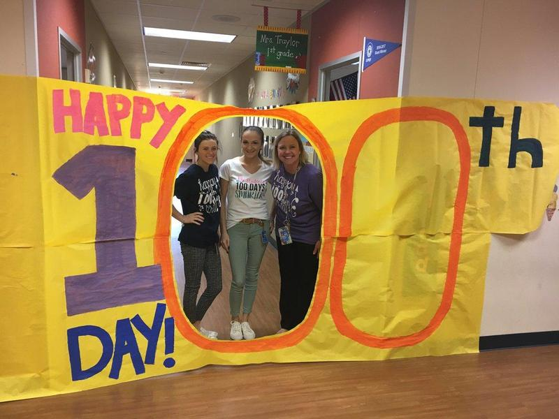 Adults standing behind 100 Days of School sign