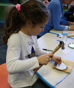 2nd grader uses hammer and nail to try tin piercing during Colonial Days at Wilson School.