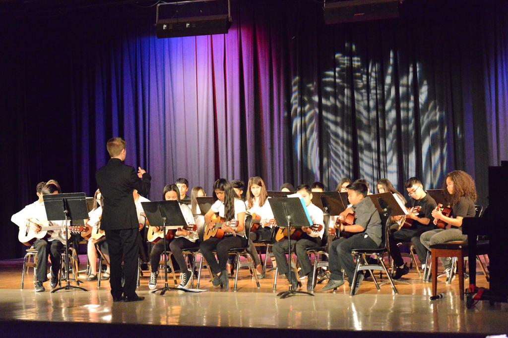 Music teacher conducting the band on stage.