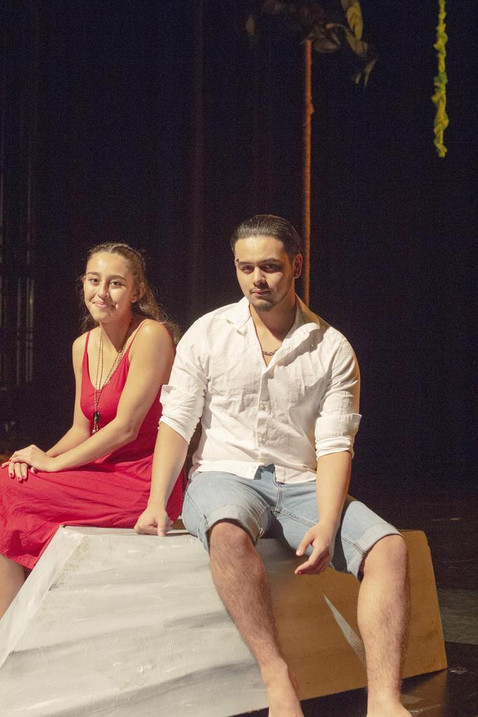 Two cast members on stage before the production