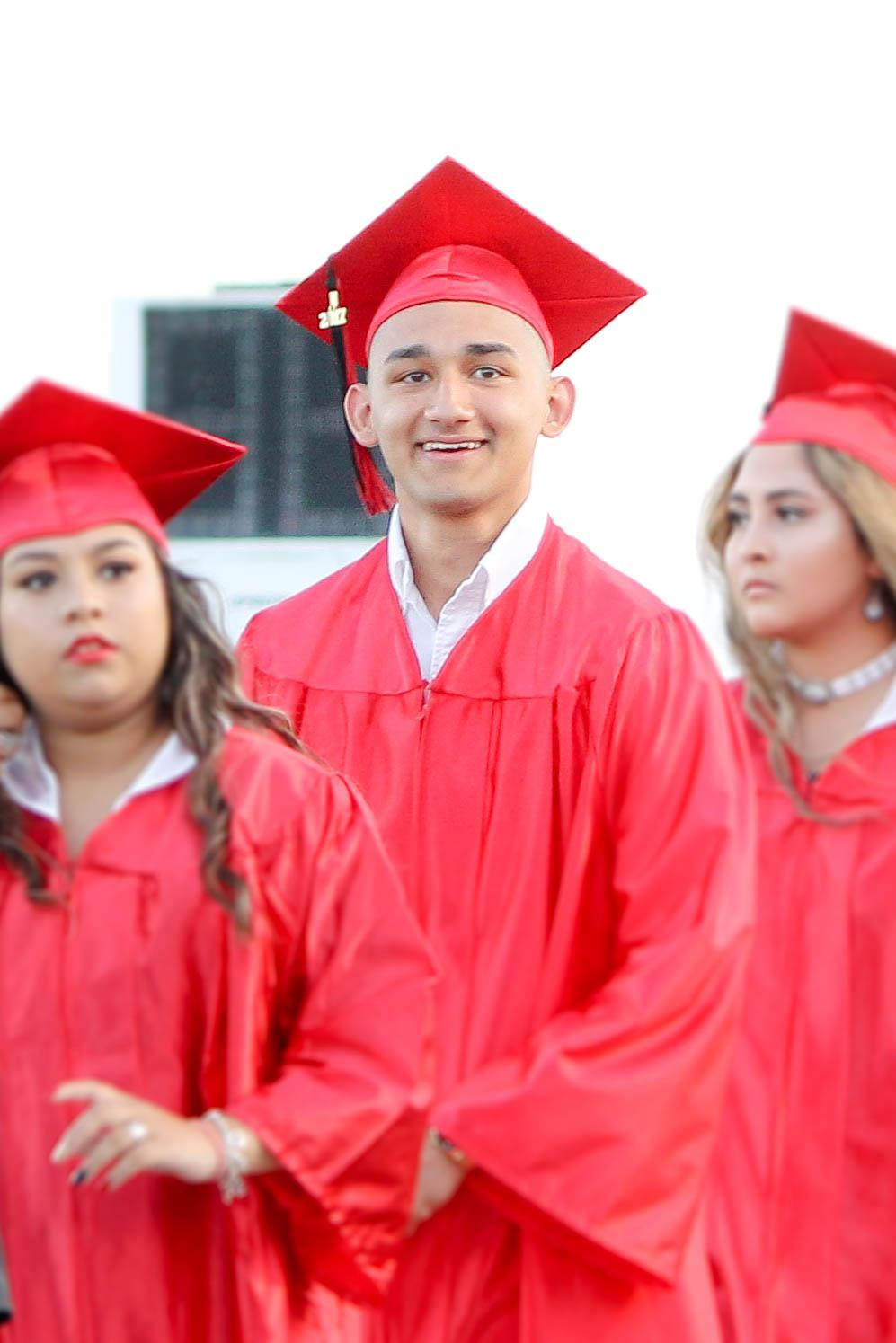 male victoria east high school student smiles at the crowd of the 2018 graduation ceremony