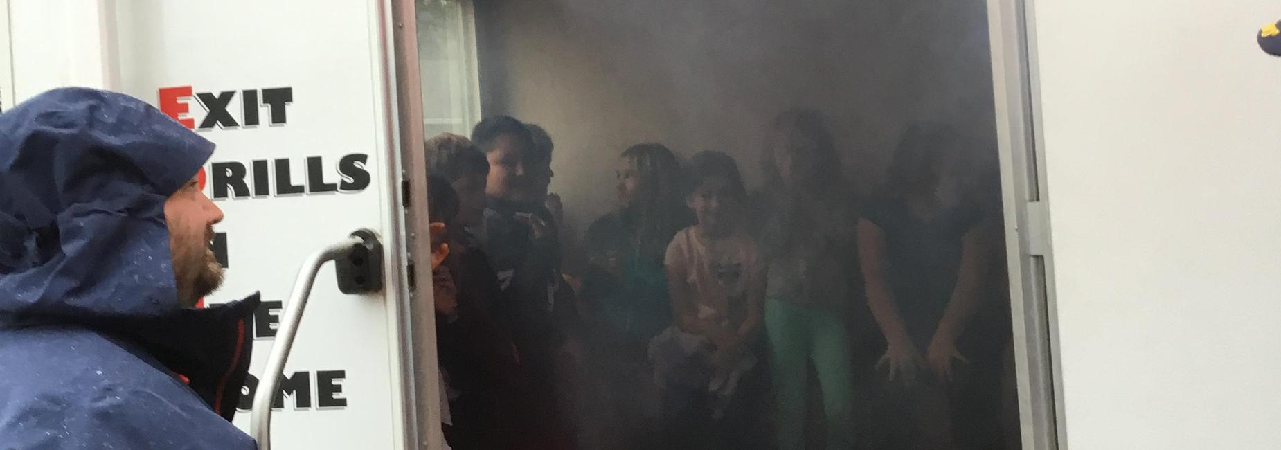 Students in a trailer with smoke around them as a simulation