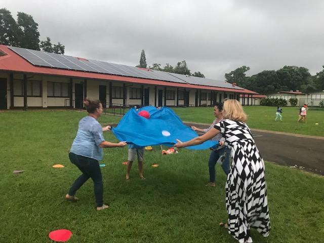 The Principal and team have fun with ball toss game.