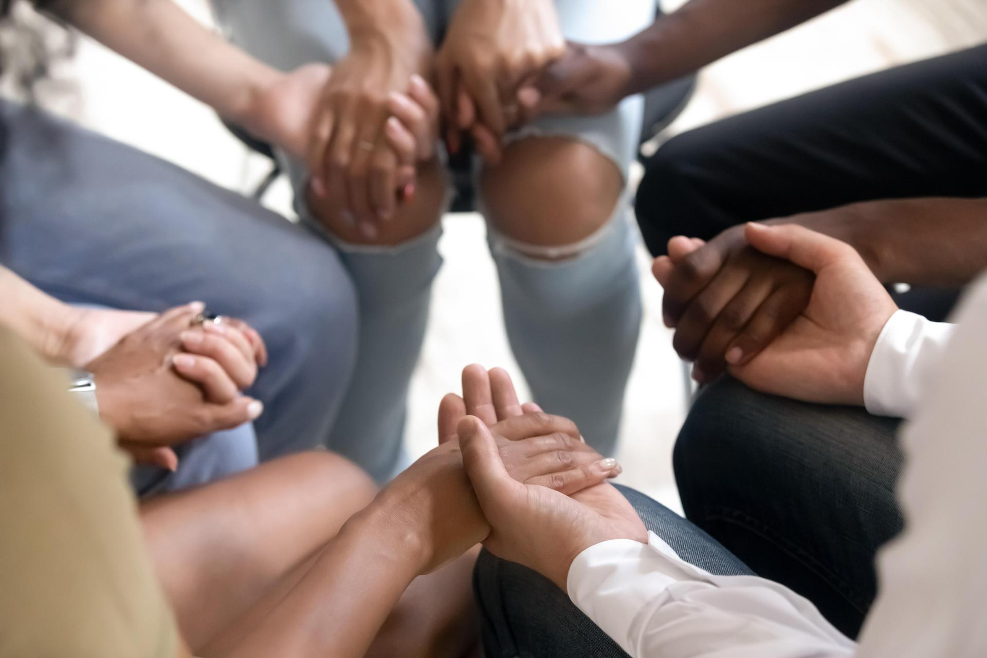 Group of adults in a circle holding hands.