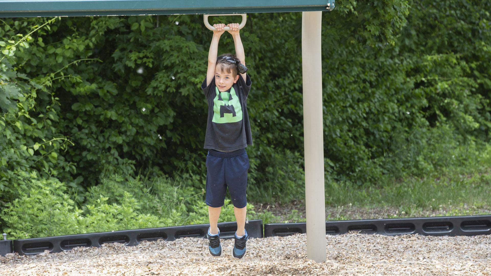 Boy hanging from playground equipment