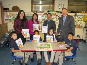 several kids holding their coloring activity book with Comm. Martinetti, Principal Celebrano, and Drug Free Representative