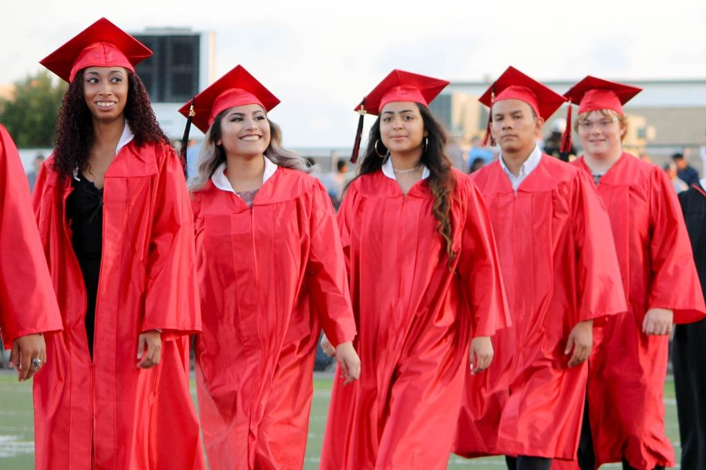 students of the victoria east high school 2018 graduating walking into memorial stadium, smiling female students