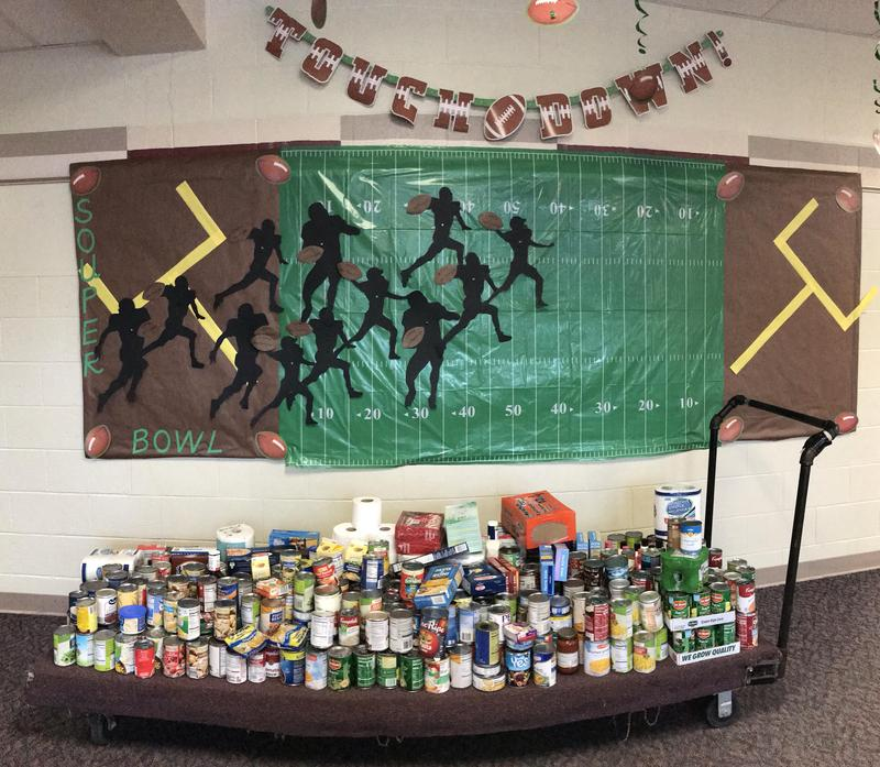 Picture of the food collected near a bulletin board for the souper bowl.