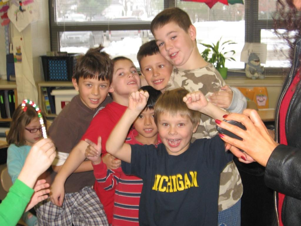 six boys pose for camera in class