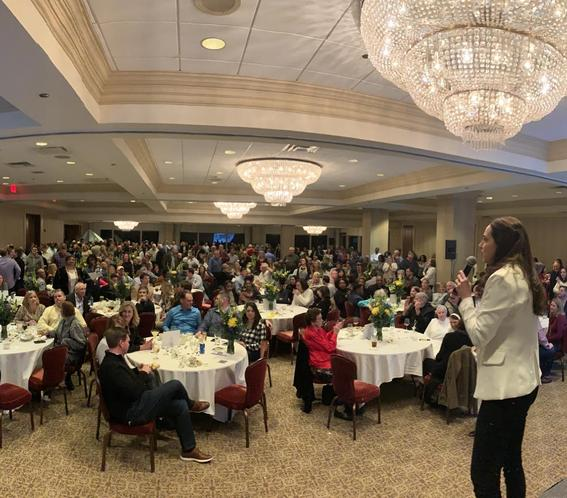 woman with microphone talking to crowd in ballroom