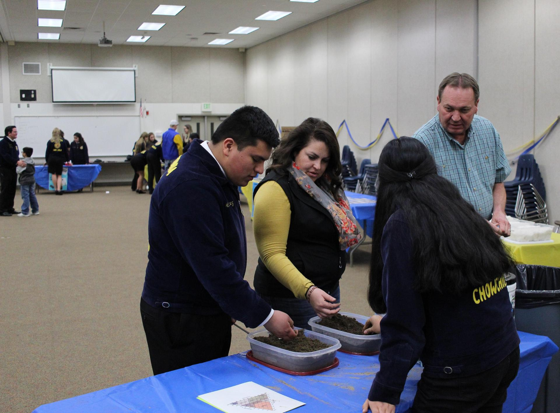 Alan Martinez, Mrs. Alkire, Maria Pichardo, and Mr. Bitter examine soil at the CDE LDE Open House in the Sachem Building