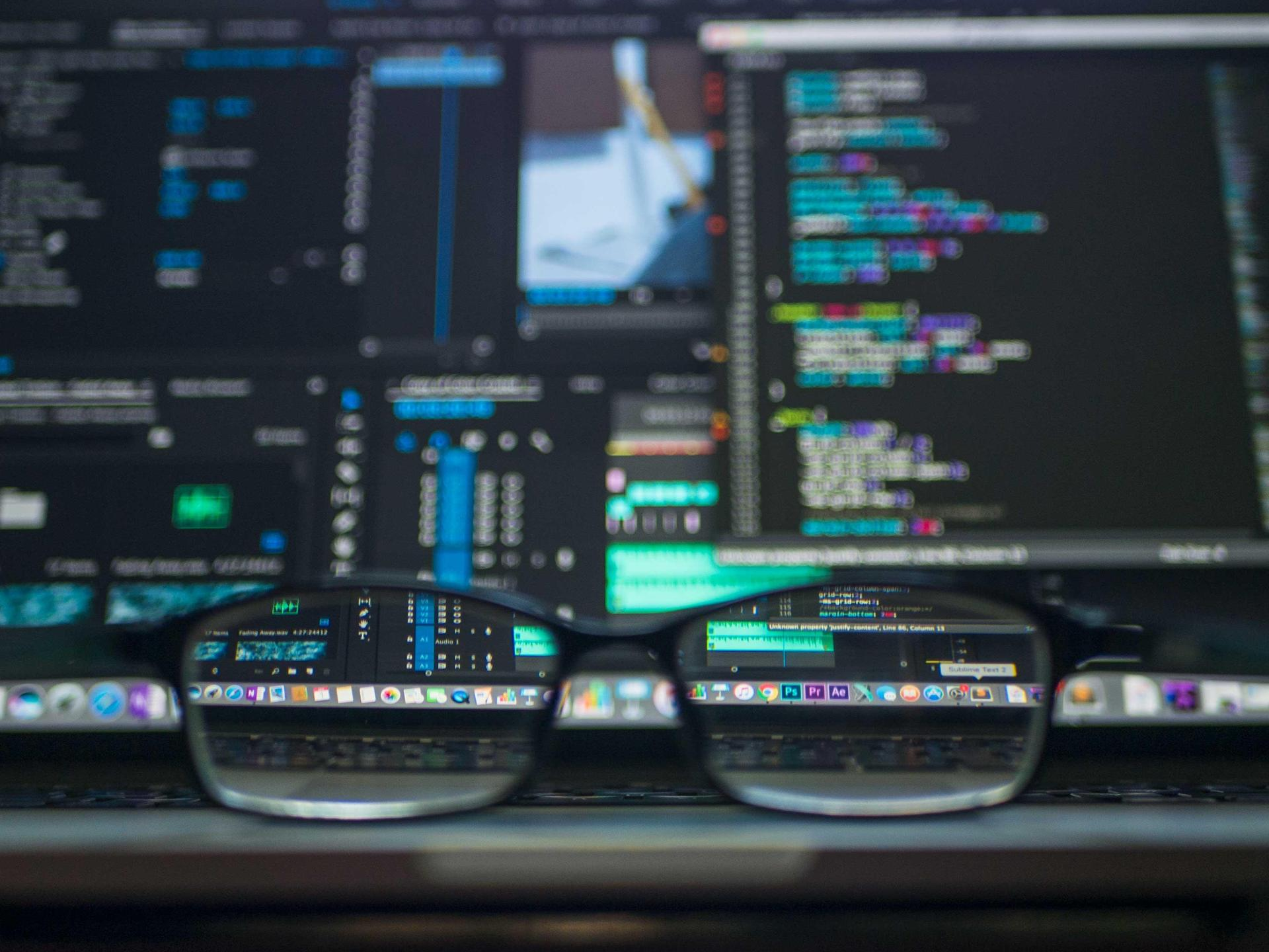 Photo of a pair of glasses with computer screens behind them