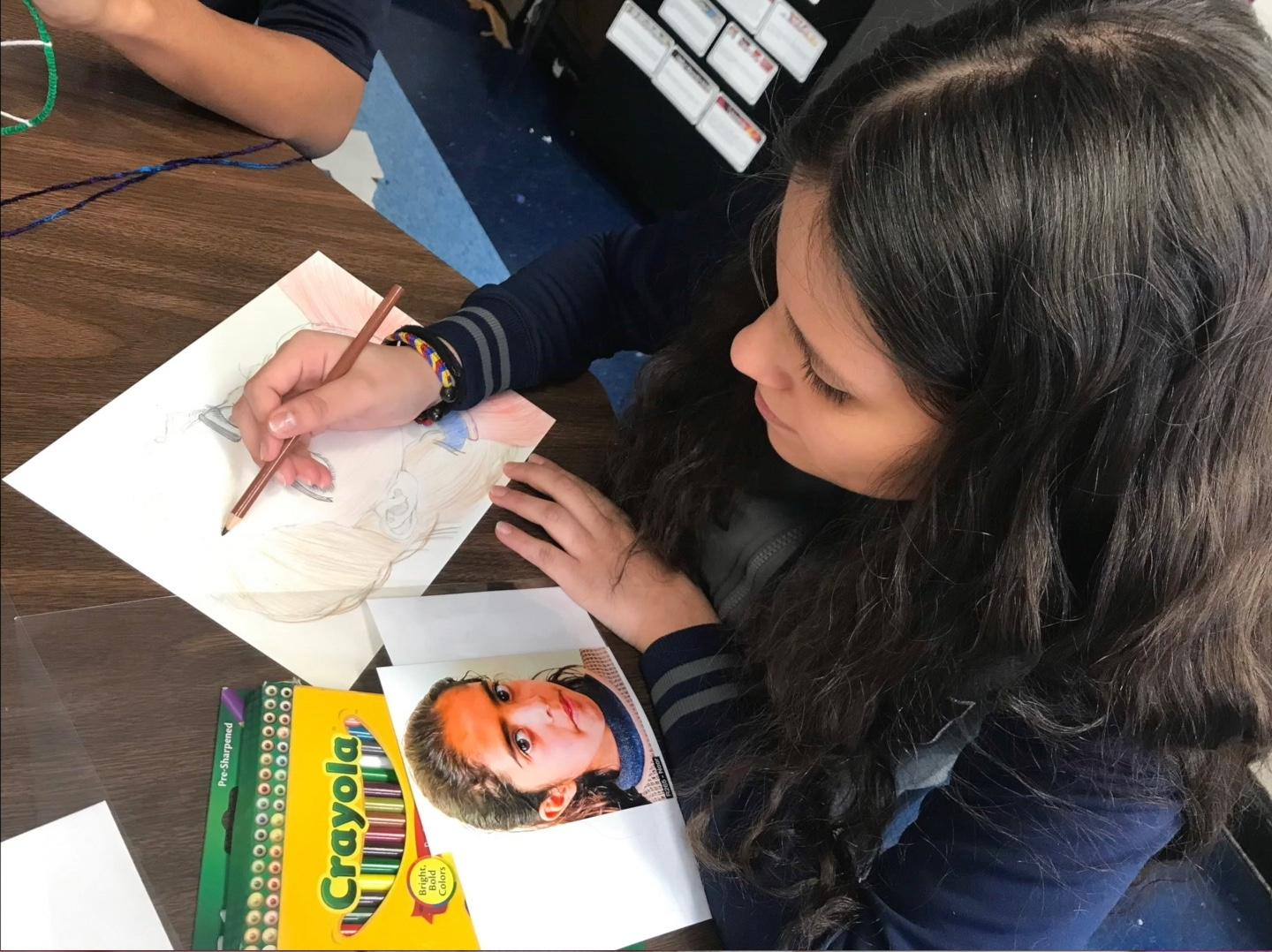 girl coloring in her portrait of a Syrian girl