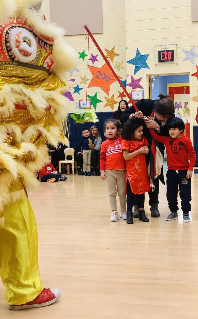 Principal Birne with a boy & 2 girls holding a stick at the large yellow Chinese Dragon