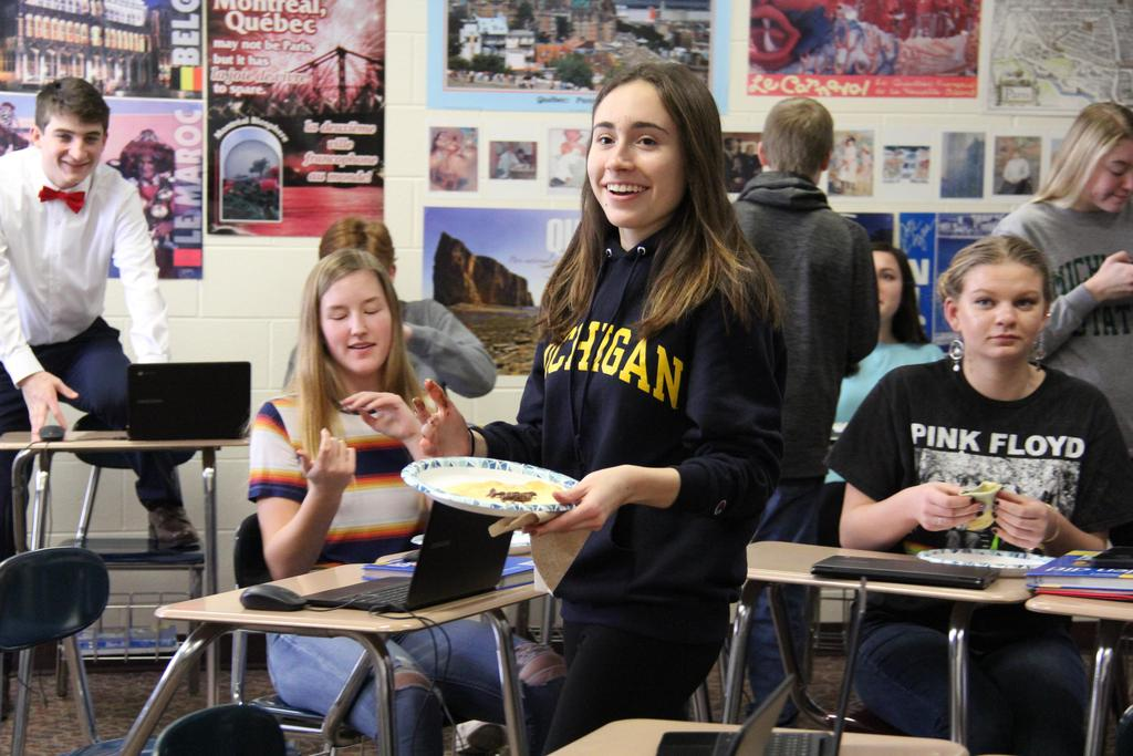 Smiling student carrying a plate of food